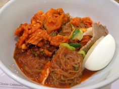 This is hoe naengmyeon, spicy chilled Korean buckwheat noodles topped with raw fish. Koreans usually eat the egg first to coat the stomach. Check out our book 'Seoul Sweet Seoul' for the best neighborhood to find hoe naengmyeon! http://amzn.to/I1gLD9