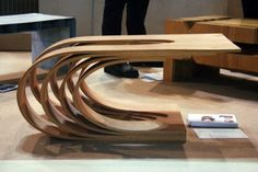 """Ghenwa Soucar - """"De-lamination Table"""" Material: Red oak Process: Steam bending and glue lamination Originally inspired by an overlapping wave pattern, this table combines two simple two-dimensional curves to develop a complex three-dimensional form. The piece consists of four layers that appear to delaminate like a flexed deck of playing cards. Each of the four layers consist of three laminations of red oak that were steam bent, then glue laminated to lock in the final form."""