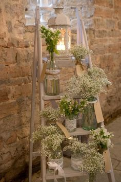 ladder lantern and flowers in glass containers.