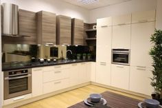 Reduced width wall cupboards work in dark colour tones as this prevents them appearing too imposing.   The light acacia laminate finish is the perfect compliment to warm cream colour tones,