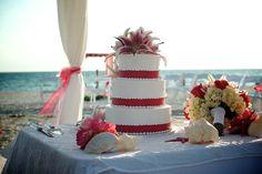 Beach wedding cake with fuchsia pink ribbon & pink stargazers