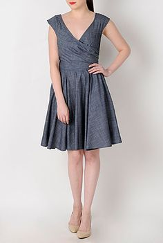 Our cotton chambray dress is fashioned with a cross-over bodice and pleated surplice underlayer to add just the right styling for our retro-inspired silhouette.