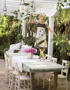 Simple wooden outdoor table with mismatched chairs.