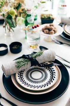 Gorgeous black and white tabletop decor with mixed print plates and fresh greenery on the napkin ties. Love