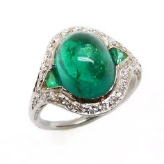 Art Deco cabochon emerald and diamond cluster ring, c.1930,  the oval cabochon stone flanked by tapered baguette emeralds and with 'eye' shaped diamond set border, collet set in platinum