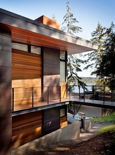 Design-and-construction firm First Lamp Architects has raised this family home near Seattle above a nearby body of water, drawing references from bridge structures.