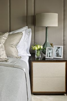 Master bedroom from Mayfair townhouse project. Luxury bedside table with drawers, brass trim. Bespoke panelled headboard. Blue green ceramic lamp with shade.