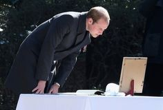 Noblesse et Royautés: Royal Tour of Japan, Day 2, February 27, 2015-Duke of Cambridge reads a newspaper clipping and note left by his mother Diana, Princess of Wales, in 1995, at the Commonwealth War Graves Cemetery in Yokohama