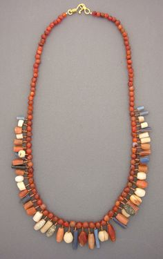 by Anna Holland | Necklace; Antique carnelian, quartz, granite, and glass beads from the African nation of Mali, originally made to be woven into women's hair, are now interspersed between a beautiful strand of antique carnelian beads. The gold-filled hook and eye clasp was handmade in Sri Lanka | Sold