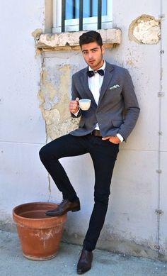 Shop this look on Lookastic: http://lookastic.com/men/looks/bow-tie-and-dress-shirt-and-blazer-and-pocket-square-and-belt-and-jeans-and-oxford-shoes/674 — Navy Bow-tie — White Dress Shirt — Grey Blazer — White Floral Pocket Square — Brown Leather Belt — Navy Jeans — Brown Leather Oxford Shoes