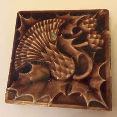 """Manufactured by Beaver Falls Art Tile Co. of Beaver Falls, PA.(1886-1927, Francis W. Walker). On the back is embossed """"14 F.A.T. Co. L BeaveFall PA."""" though it is difficult to read in places. Has a few chips and some wear. 