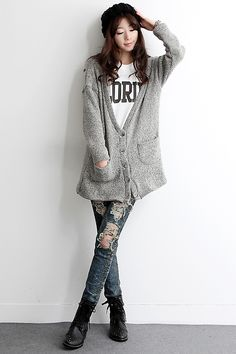 Black beanie, oversized grey cardigan, white graphic t-shirt, ripped blue jeans, black boots.