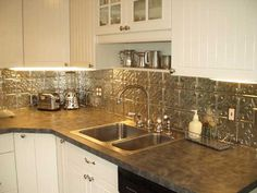 Use tin ceiling tiles to create an affordable & easy-to-install backsplash for a country kitchen.