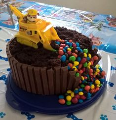 "Rubble Paw Patrol cake. 2 layer chocolate cake. Don't use frosting on the top of the cake. Simply ""rake"" the top of the cake with a fork to give it the dirt look. Chocolate frosting around and between the cake to hold the kitkats in place and the M&Ms down the side. VERY simple easy cake to make. I used saran wrap under the toy."
