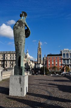 Looking out onto the Historic District of Antwerp, sculpture, bridge, cobble stones and church  #belgium