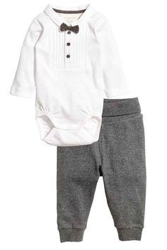 Body i spodnie: Komplet z miękkiej mieszanki zawierającej ekologiczną bawełnę. Body z długim rękawem i kołnierzykiem. Gors frakowy z guzikami u góry, zatrzaski w kroku. Spodnie z szerokim, odwijanym ścigaczem w talii, ściągacz u dołu nogawek. Czarne mają lampasy.