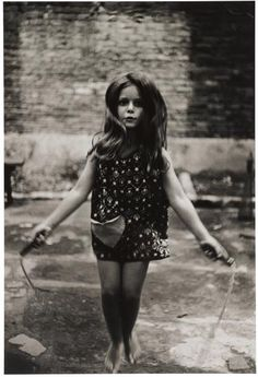 DIANE ARBUS  Barefoot Child Jumping Rope, NYC  1963  Gelatin silver print.  9 1/4 x 6 1/4 in. (23.5 x 15.9 cm)  Stamped 'a diane arbus print', signed by Doon Arbus, Executor, in ink, copyright credit and reproduction limitation stamps on the verso. Accompanied by a Certificate of Authenticity from the Estate of Diane Arbus.