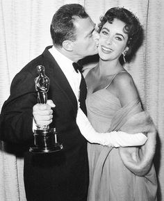 "Mike Todd kisses his wife, Elizabeth Taylor, as he holds his Oscar for ""Around the World in 80 Days"" at the Academy Awards in March 1957."