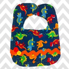 Navy dinosaur fabric with mutli-color striped backing, and warm and natural in the center, snap closure, baby boy bib