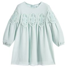 This lovely turquoise blue Mini-me dress by Chloé is made in slightly textured crêpe with beautifully embroidered lace appliqués all around the bodice and arms. It is both casual and smart, with gathered, bell sleeves and the designer's logo on the hemline.