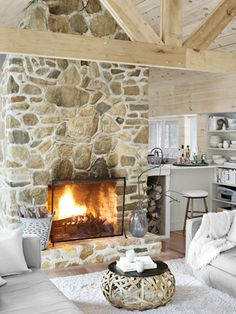 In the den of this Massachusetts cabin, a stone fireplace is accessorized with a handblown glass vase and a vintage kindling bucket.