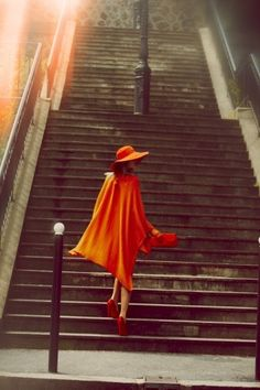 Beautiful photo of a lady in orange on grey stairs. My favorite color combo: orange and grey.