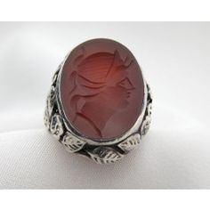 Circa 1900. This is a beautiful Arts & Crafts ring centered by a carnelian intaglio.  The intaglio carving is of a Roman or Greek soldier in profile. An elegant leaf design decorates the mounting of the ring.