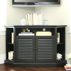 Support your television and safeguard your home entertainment resources with this sturdy black wood TV stand. The louvered doors close neatly to hide away your DVDs, games and other items that usually