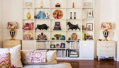 One Kings Lane style blog features tips on bookshelves. These are well grounded, light on top and heavier down below. Books are loosly collected by color. The dramatic bulls facing off in the middle are the true stars here.