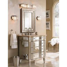 A Glamorous Bathroom With Plenty Of Mirrors And Mirrored Furniture