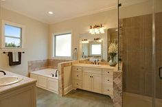 Master bath has separate vanities, garden tub, and custom tiled shower.