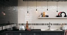The main work area of this kitchen is tiled in black and white tiles that complement the distressed charcoal cabinets. A stripe of black, white, and gray tiles runs two tiles above the countertops, breaking up the flat colors of the rest of the walls. Interior, Tile Design, Black Porcelain Tiles, Luxury Kitchens, Wall Tiles Design, Subway Tile Design, Artistic Tile, Best Kitchen Designs, Luxury Kitchen Design