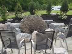 Natural Boulder fire pit designs | boulder fire pit in irregular flagstone patio cicero