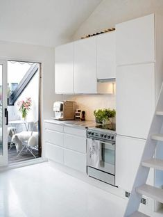 Small minimalist open space kitchen in living room corner. Simple and useful with the oven/hob, fridge hidden and a lot of space to put away your dishes still.