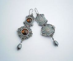 The inspiration for those earrings came from Baroque jewelry. Those earrings are made of Swarovski crystals, braided with dark sivler- and nikel-plated glass beads and Swarovski imitated pearls on nylon thread. Niobium-silver Tierracast furniture. The earrings are 9 cm long.