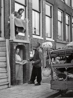 Handelaar in huishoudelijk artikelen toont mattenklopper aan twee huisvrouwen. Nederland, Amsterdam, 1953.  Man selling household ware to Dutch housewives. Amsterdam, 1953.