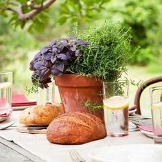 Natural appeal: Keep the ambience natural with elements such as a handsome wooden table topped with a natural-fiber tablecloth. A terra-cotta pot holds herbs. Freshly baked bread makes a mouthwatering centerpiece for this dinner party.