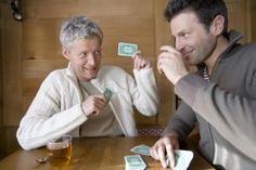 Mature man and man playing cards in chalet, smiling - Schultheiss Selection GmbH & CoKG/The Image Bank/Getty Images