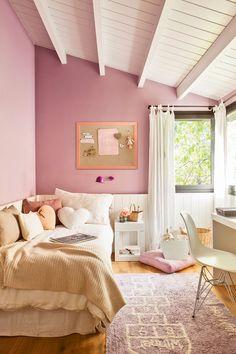 Habitación infantil abuhardillada con paredes en rosa y tehcho de madera en blanco