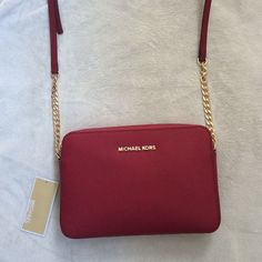 "NWT Michael Kors jet set travel large cross body In cherry gold. I'm open to reasonable offers. Saffiano leather. Adjustable cross body strap with 25"" drop. Top zip closure. 9"" W x 6"" H x 2"" D. 2 available Michael Kors Bags Crossbody Bags"