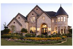 A rounded, two-story turret with closely spaced windows adds rich character to this brick and stone new home from Toll Brothers. In The Reserve at Colleyville, near Fort Worth.
