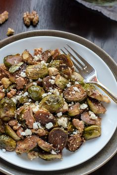 A quick and easy vegetable side dish of Brussels sprouts roasted with balsamic vinegar and maple syrup, then tossed with toasted walnuts and feta cheese. @LawStudentsWife