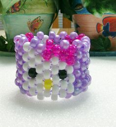 Kandi Stretch Beaded Cuff Bracelet In Hello Kitty Design With Lilac Background And Pink Bow This bracelet will fit up to wrist Collect, Trade, Gift This piece will get you lots of compliments at a Rave or Festival Lilac Background, Kandi Cuff, Beaded Cuff Bracelet, Hello Kitty, Bows, Birthday, Pink, Gifts, Handmade