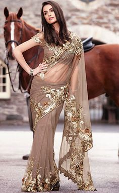 # Dazzling fawn color net saree with blouse.  # Saree is approving with stone work, zari, resham and sequins.  # You can wear on party and wedding occasion.
