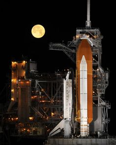 Photograph by Bill Inglais (NASA) - A nearly full moon sets as the space shuttle Discovery sits atop Launch pad 39A at the Kennedy Space Center in Cape Canaveral, Florida, in the early morning hours of Wednesday, March 11, 2009.