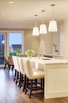 Two Clear Glass Globe Light Pendants Illuminate A White Kitchen Beauteous Kitchen Island Chairs Design Ideas