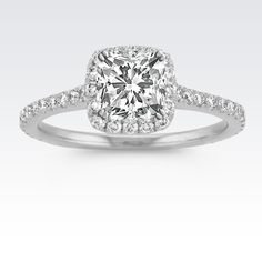 As part of our exclusive Eternally Yours collection, this halo engagement ring is especially created to hold your chosen diamond 1.00 carat cushion cut, asscher cut, round or princess cut diamond in a low flush fashion. Fifty-eight round diamonds, at approximately .46 carat total weight, are pavé-set in quality 14 karat white gold and brilliantly accent the setting. Look to the profile of this amazing setting to see the accent of diamonds among the bridge of the ring.