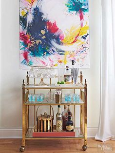A vintage brass bar cart pairs with a modern art canvas created by a local high school student. A fan of making your own art, Jen says to play some music and let yourself be free. It's an inexpensive way to break the mold and with dramatic outcome.