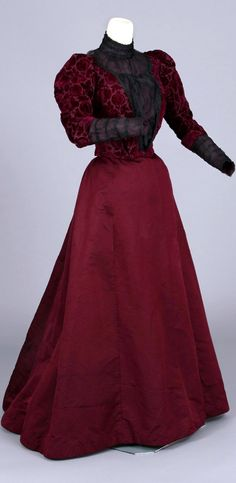 Dress, two pieces, ca. 1890-1909. Voided velvet, black chiffon, purple. Striking voided velvet pattern with pomegranate design. Skirt is ribbed silk and bodice has gathered black chiffon cuffs, puffed sleeves, and pigeon breasted-blouse front that would persist in popularity into the early 1900s. Chester County (PA) Historical Society