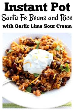 Instant Pot Santa Fe Beans and Rice–brown rice, kidney beans and black beans are simmered with salsa, corn and seasonings in your electric pressure cooker. The beans and rice are topped with garlic lime sour cream and grated cheddar cheese. You can serve this as a meatless meal or add in chicken for some extra protein. We love this easy and healthy, family friendly meal.#instantpot #instapot #pressurecooker